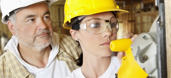 Female worker cutting wood with a power saw while male worker standing behind